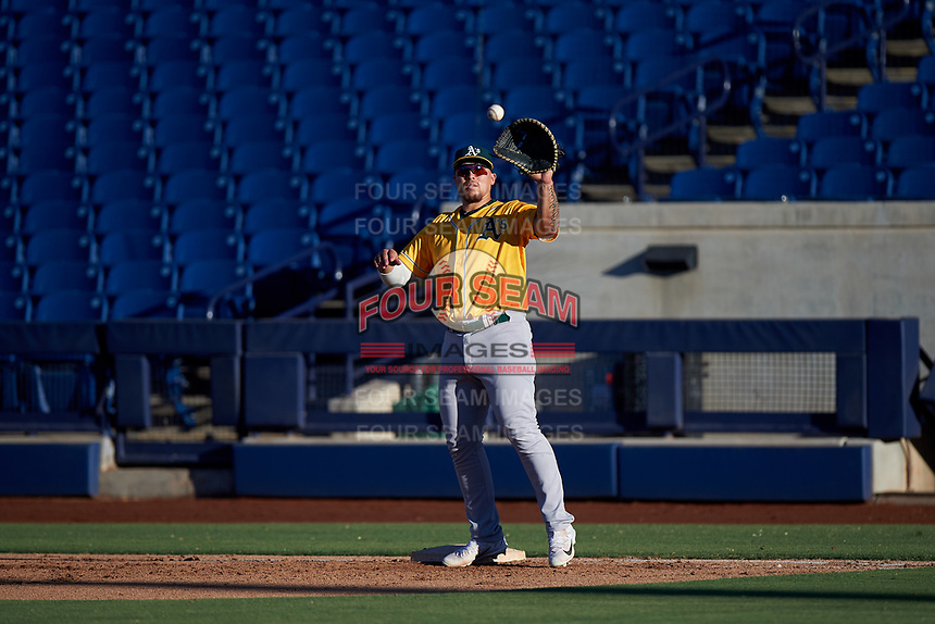 AZL Athletics Gold first baseman Gio Dingcong (14) warms up between innings of an Arizona League game against the AZL Brewers Blue on July 2, 2019 at American Family Fields of Phoenix in Phoenix, Arizona. AZL Athletics Gold defeated the AZL Brewers Blue 11-8. (Zachary Lucy/Four Seam Images)