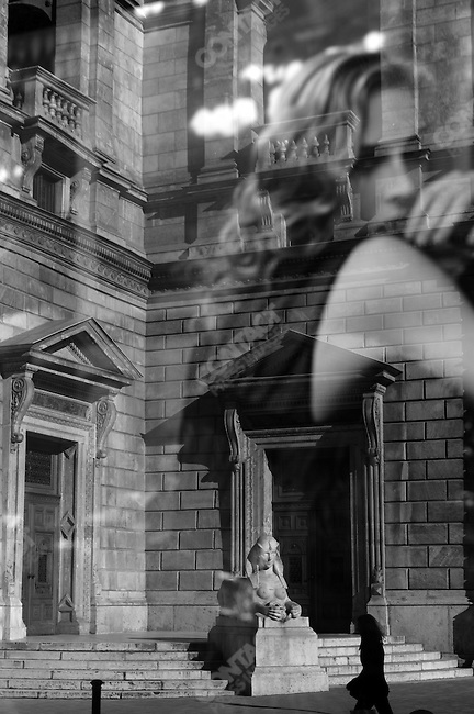 A woman and the Opera House in Budapest were reflected in the window of the Louis Vuitton store on Andrassy Road which had a photograph of Madonna advertising its products. Budapest, Hungary, March 24, 2008