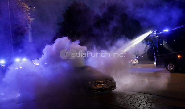 A police water cannon is used to put out a car fire during demonstrations against the G20 summit in Hamburg, Germany, 6 July 2017. The heads of the governments of the G20 group of countries are meeting in Hamburg on the 7-8 July 2017. Photo: Kay Nietfeld/dpa /MediaPunch ***FOR USA ONLY***
