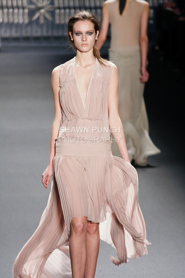 Jac walks runway in a dusty pink chiffon multi-pleated deep V-Neck gown with high-low hem, from the Vera Wang Fall 2011 collection, during Mercedes-Benz Fashion Week Fall 2011.
