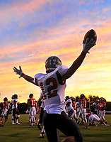 Fauquier's Cole Anderson celebrates a first half touchdown as the sky at Heritage High School is momentarily painted with bright colors.