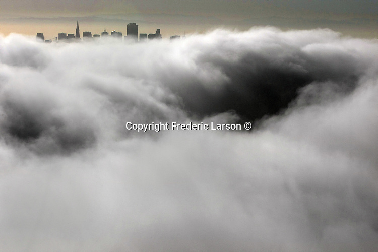 The incoming fog blankets the bay and skyline of San Francisco, California.