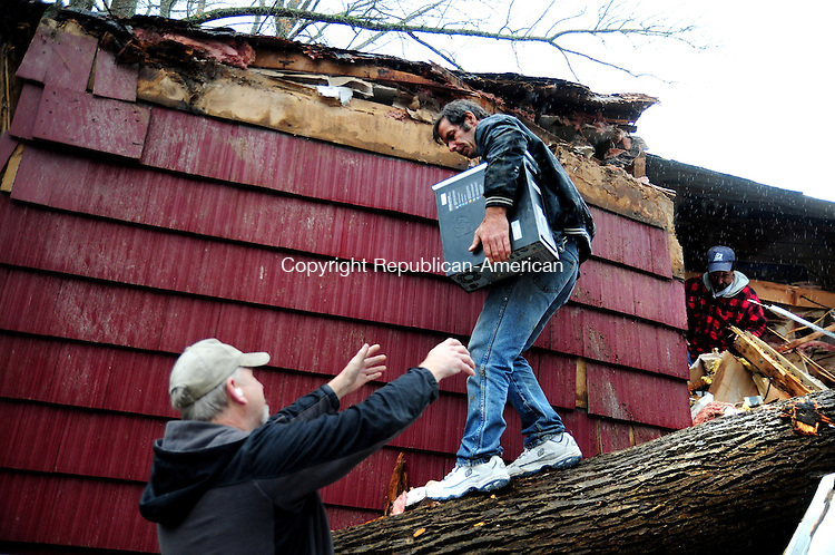 NEW MILFORD, CT, 30 OCT 12-103012AJ10- Arthur Bertram carries a computer out of his trailer home in New Milford Tuesday morning after it was crushed by a tree Monday evening.  Alec Johnson/ Republican-American