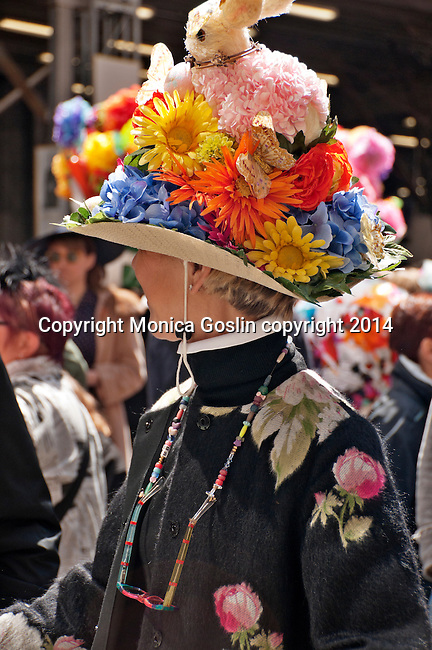 Woman wearing a flowered coat and a large hat decorated with flowers and and a bunny rabbit in the Easter Parade on Fifth Avenue in New York City