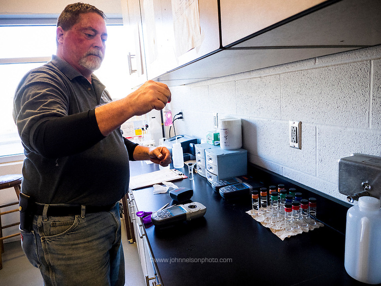 Bill England, Utility Services backflow technician, at Lake Station's water filtration plant, tests the PH level in a sample of  treated water.