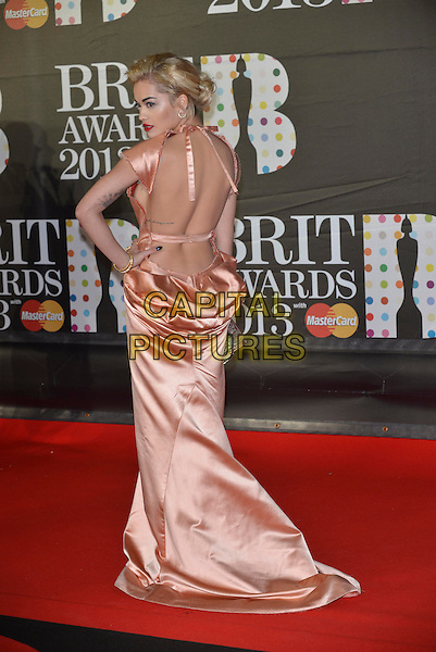 Rita Ora.The Brit Awards 2013 arrivals at the O2, Greenwich, London, England 20th February 2013.The Brits  full length peach dress silk satin halterneck ruched long maxi hand on hip gold back rear behind strap tattoos cut out low backless train.CAP/PL.©Phil Loftus/Capital Pictures.