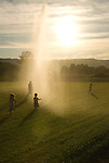 Children playing in a field with back lit sprinklers at Kruger Farm, Sauvie Island, Oregon