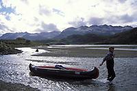filmmaker and photogapher Andreas Kieling hauls a canoe as a grizzly bear, Ursus arctos middendorffi, fishes for salmon in Katmai National Park, southcentral Alaska, USA