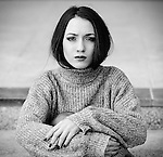 Young woman with contemporay look wearing winter sweater looking at camera