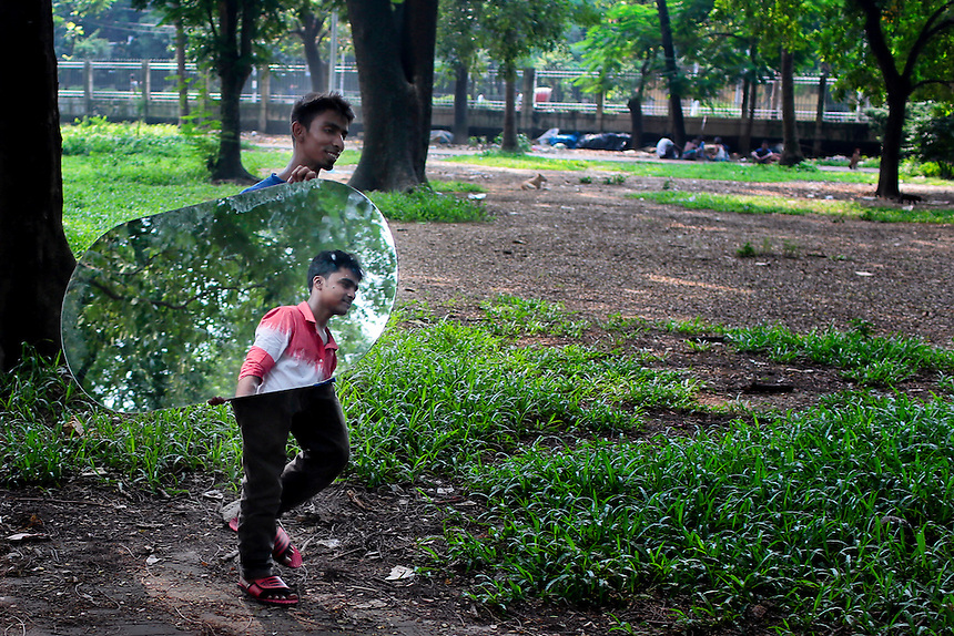 A Bangladeshi boy carries a mirror and other reflects, as they walk cross a park in Dhaka, Bangladesh.