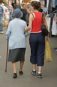 A young woman walks with her grandmother in a small town in southern France on market day