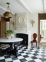 The front hall's Indian table and English chandelier and chair are 19th-century and the 17th-century fire- place is limestone; the black and white check pattern marble flooring is by Exquisite Surfaces.
