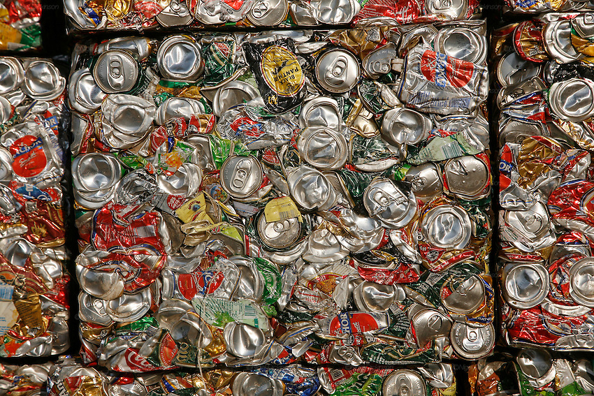 Bricks of squashed aluminum cans are stacked waiting for export. Recycling warehouse, big distribution for aluminium cans, and general metals, on the edge of Phnom Penh. Aluminium cans are sold with a street value of about 1$ the kilo, the small warehouse add 10% and all the cans are shipped. already sorted to the big distribution recycling warehouses outside Phnom Penh. Here the aluminium cans are squashed into bricks and stacked or placed in mountains for export to Thailand and Vietnam for truning back into the raw material.