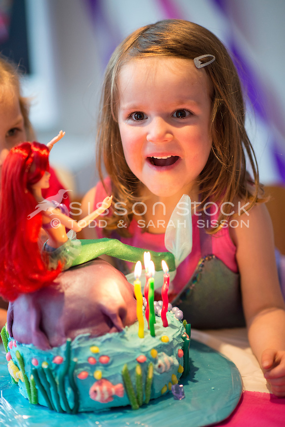 Five year old girl looking surprised at her mermaid decorated bithday cake, New Zealand - stock photo, canvas, fine art print