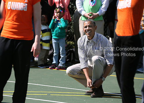 United States President Barack Obama ties his shoe while playing basketball with children during the annual Easter Egg Roll on the White House tennis court April 1, 2013 in Washington, DC. Thousands of people are expected to attend the 134-year-old tradition of rolling colored eggs down the White House lawn that was started by President Rutherford B. Hayes in 1878. .Credit: Mark Wilson / Pool via CNP