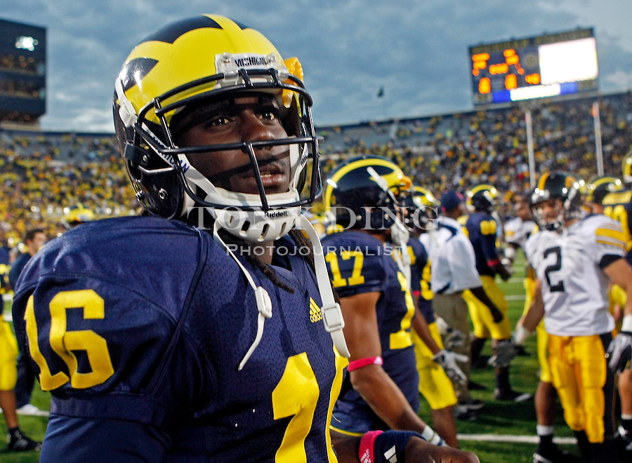 Michigan quarterback Denard Robinson (16) walks off the Michigan Stadium field after an NCAA college football game with Iowa, Saturday, Oct. 16, 2010, in Ann Arbor, Mich. Robinson went out of the game early in the third quarter from an injury in Iowa's 38-28 win. (AP Photo/Tony Ding)