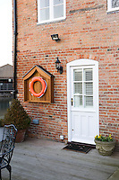 A lifebuoy hangs on the brick wall next to the front door of John Coles' converted canalside warehouse in Nottingham