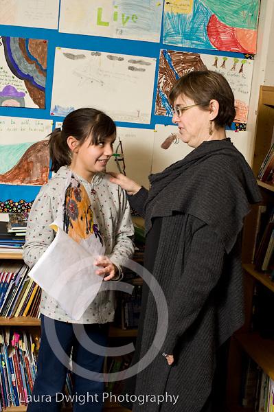 Elementary School New York Grade 4 female teacher praising female student on her work vertical