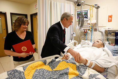 Bethesda, MD - July 3, 2008 -- United States President George W. Bush meets with  U.S. Marine Corps Sergeant Major Patrick Wilkinson and his wife, Jennifer, of Temecula, California, Thursday, July 3, 2008, at the National Naval Medical Center in Bethesda, Maryland, where President Bush presented Wilkinson with a Purple Heart medal..Credit: Eric Draper - White House via CNP