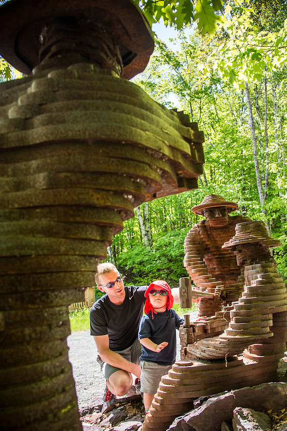 A young family explores a mining themed sculpture along the Iron Ore Heritage Trail at Negaunee, Michigan.