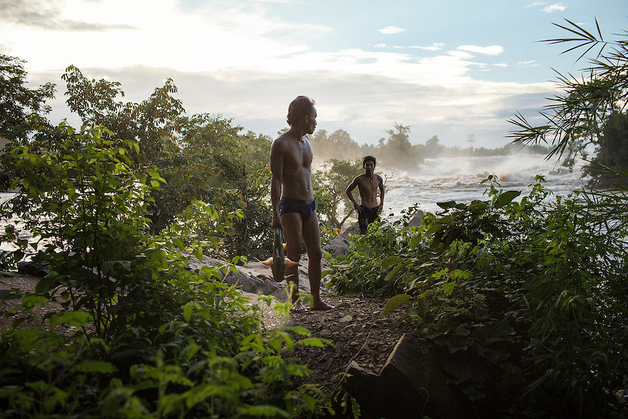 Two fishermens emerge from the water of the Khone Phapheng falls with their catch. 04/08/2013 © Thomas Cristofoletti / Ruom