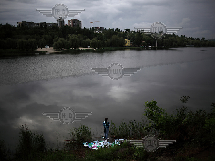 A young man fishing on the Kalmius River.
