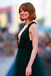 Emma Stone poses on the red carpet at the opening of the 71st Venice Film Festival in Venice, on August 27, 2014.