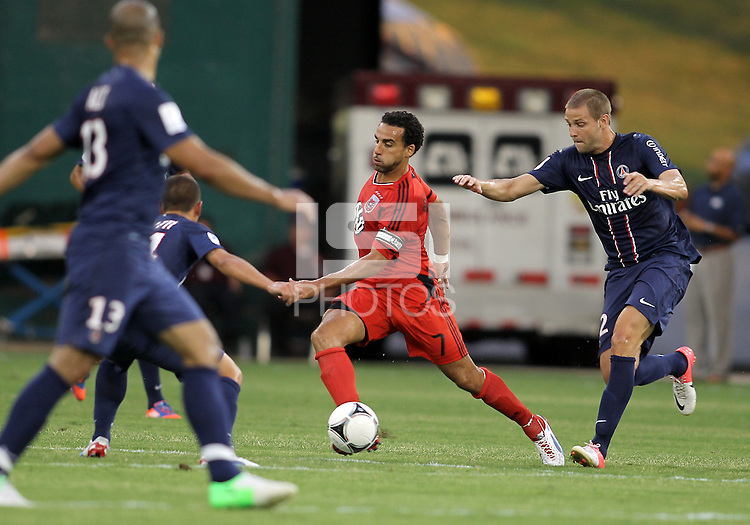 WASHINGTON, DC - July 28, 2012:  Dwayne DeRosario (7) of DC United cuts past Mathieu Bodmer (12) of PSG (Paris Saint-Germain) in an international friendly match at RFK Stadium in Washington DC on July 28. The game ended in a 1-1 tie.