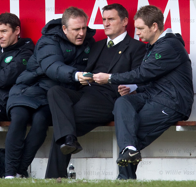 Tony Mowbray is stoic as assistants Mark Venus and Peter Grant pass notes to each other