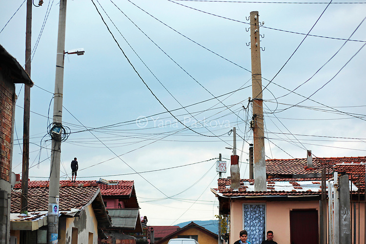 A man stands on a rooftop below a handmade electrical grid hanging over a Roma village, as people turn up to vote in October's Parliamentary elections in the nation's capital, Sofia. Today, October 5th, 2014, is also Midterm Elections day in the States - its multi-party ticket an unimaginable reality in autocratic Bulgaria pre-1989. Despite a month-long vacillation on the make-up of their political coalitions and their new prime minister - and that only 49% of the population turned up to vote today - party leaders narrowly avoided reelections, with former prime minister and leader of center-right party GERB Boyko Borisov reinstated at the post.<br /> <br /> This photo is from a project that aims to gauge the state and effect of democracy in the former Soviet satellite nation Bulgaria, two and a half decades after the fall of the Berlin Wall. The story of democracy in Bulgaria at age 25 is a cautionary tale about transplanting one-size-fits-all Western values to a nation still undergoing social and economic upheaval. Bulgaria is still one of the poorest, most corrupt nations in the European Union, its post-1989 hopes wilted by political instability, high crime rates and skyrocketing inflation. While Bulgarians can now freely vote and protest without much threat to their freedom, their new oppressor is corruption - which is at a 15 year high, across political and civil sectors alike. The ennui is so casually etched on the passerby's face that it becomes routine - one that fits in sadly well against a startling backdrop of rotting architecture, joblessness, and a vast population decline. Despite what democracy has changed in Bulgaria, the daily struggles of its populace remain largely untouched, trapped in a post-communist time capsule.