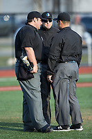 The umpiring crew gets together to discuss a call during the NCAA baseball game between the Rutgers Scarlet Knights and the Iona Gaels at City Park on March 8, 2017 in New Rochelle, New York.  The Scarlet Knights defeated the Gaels 12-3.  (Brian Westerholt/Four Seam Images)