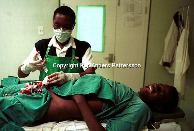 "dicuinit00025 Culture. Initiation. Ayanda Mzukwa, age 18, feels the pain as he is circumcised properly by a doctor on July 7, 2001 in Mount Ayliff in Easter Cape Province, South Africa. Every year, thousands of Xhosa men go to the bush for about 3-4 weeks to become men. They are circumcised the first day and are not allowed to eat or drink for the first seven days. It has become a lucrative business and many unskilled ""doctors"" put pressure on the boys and their family's to do it at an early age. Some traditional nurses use a razor blade for several boys and the infection rate is high for HIV-Aids. 170 boys from initiation school in Mount Ayliff ended up in hospital as their minders did a bad job. Some boys are are damaged for life as they can't have a normal sexlife..Photo: Per-Anders Pettersson/ iAfrika Photos"