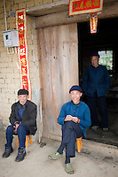 Elderly men sit together in Fuli Old Town, Xingping, China