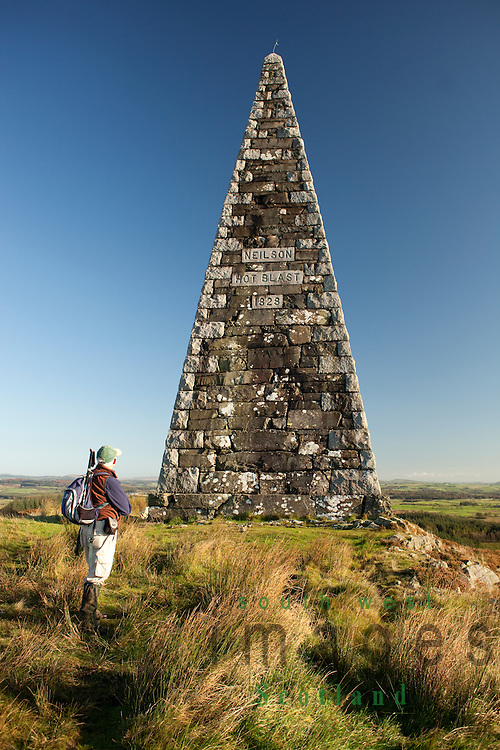 Autumnal landsape walk in Galloway. Walker standing on Barstobrick Hill looking up at Neilson Monument near Ringford