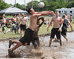 July 8, 2017- Tuscola, IL- Ben Dixon passes the ball as he collides with Silas Hortin in the mud volleyball tournament during the 2017 Tuscola Sparks in the Park celebration. [Photo: Douglas Cottle]