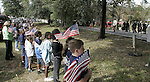 The children and teachers from Chaires Elementary School line the road and hold American flags as the funeral procession for U.S. Marine Lance Cpl. Daniel B. Chaires makes its way to the gravesite at the Chaires homestead Nov. 2, 2006.  The Chaires community is outside Tallahassee, Florida.