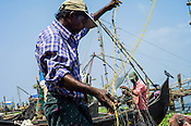 Fisherman untangle their nets on the sea shore in Kochi, Kerala, India.