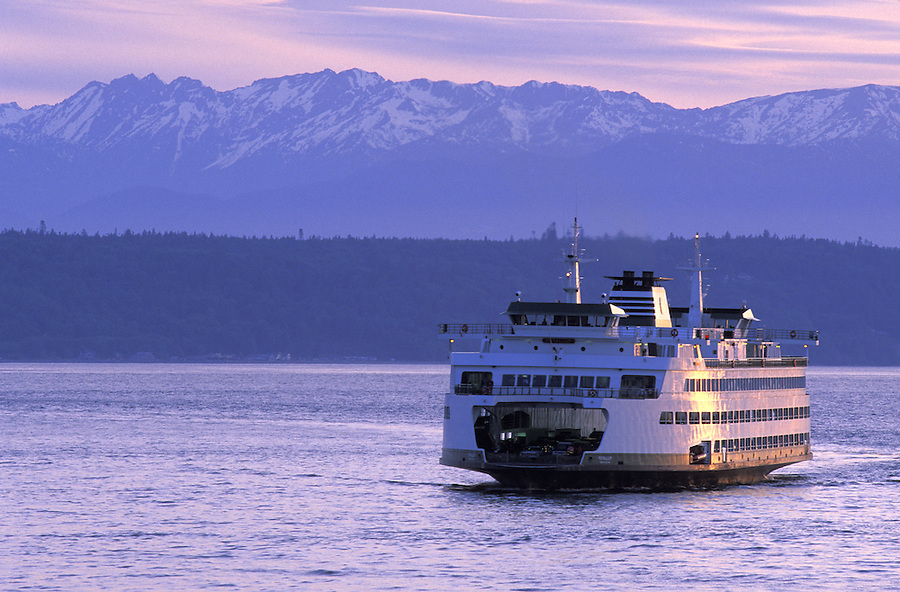 Washington State ferry Puyallup pulling into Edmonds, Washington, during sunset with Olympic Mountains in background