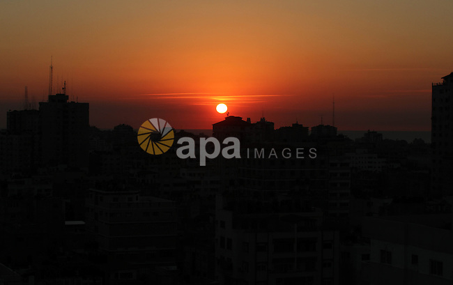 An Image shows the sunset between buildings in the western of Gaza City, Thursday, Nov. 15, 2012. Israel barraged the Gaza Strip with airstrikes and shelling Wednesday and killed the Hamas military chief in a targeted strike, launching a campaign aimed at stopping rocket attacks from Islamic militants. The assault killed 10 other Palestinians, including two children and seven militants. On Thursday, militant rockets fired into Israel killed three Israelis, raising the likelihood of a further escalation. Photo by Majdi Fathi