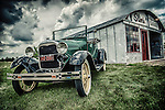 Vintage Model T Ford parked outside tin garage called Slim's on grass under cloudy sky