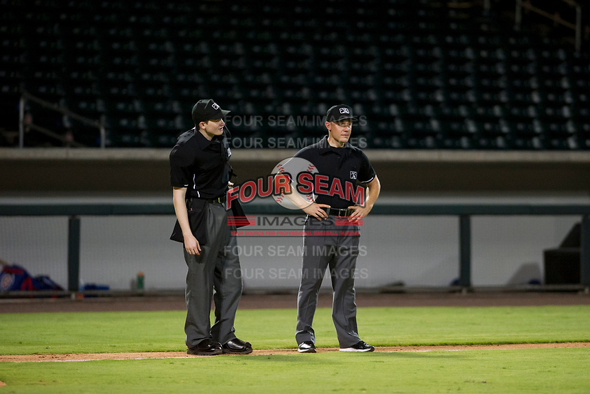 Minor league baseball umpires Patrick Faerber and Bobby Tassone talk to one another between innings of a game between the AZL Padres 2 and the AZL Cubs on August 28, 2017 at Sloan Park in Mesa, Arizona. AZL Cubs defeated the AZL Padres 2 9-4. (Zachary Lucy/Four Seam Images)