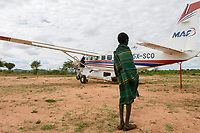 UGANDA, Karamoja, Kaabong, Karimojong boy and Cessna aircraft of MAF Mission Aviation Fellowship, a airline for missionaries, NGO, humanitary aid / MAF Flugzeug auf dem airstrip