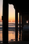 La Jolla, California; a colorful, sunset sky viewed through the pilings of Scripps Pier as it extends out over the Pacific Ocean