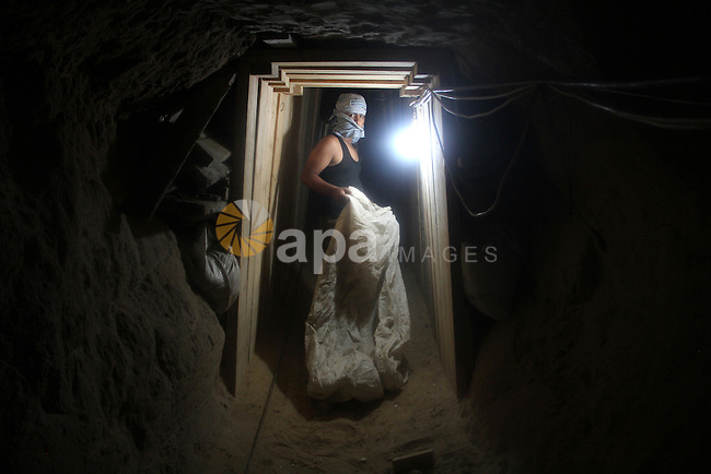 Palestinian tunnel digger, wearing a mask to conceal his identity, removes sand in a bucket from a tunnel underground in Rafah, in the southern Gaza Strip, on the border with Egypt on Sep. 4, 2011. Egyptian military Corps of engineers and border guards have began an operation designed to close a network of tunnels along the Egypt-Gaza border following tension with Israel over security along the border, security officials said. Photo by Hatem Omar
