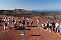 Spain, Canary Island, Lanzarote, near Yaiza: Parque Nacional de Timanfaya (Timanfaya National Park) - Islote de Hilario - tourists sampling hot volcanic gravel | Spanien, Kanarische Inseln, Lanzarote, bei Yaiza: Islote de Hilario im Timanfaya Nationalpark (Parque Nacional de Timanfaya), um die unterirdische, vulkanische Hitze zu demonstrieren gibt ein Parkranger jedem Besucher etwas heissen Vulkansand in die Hand