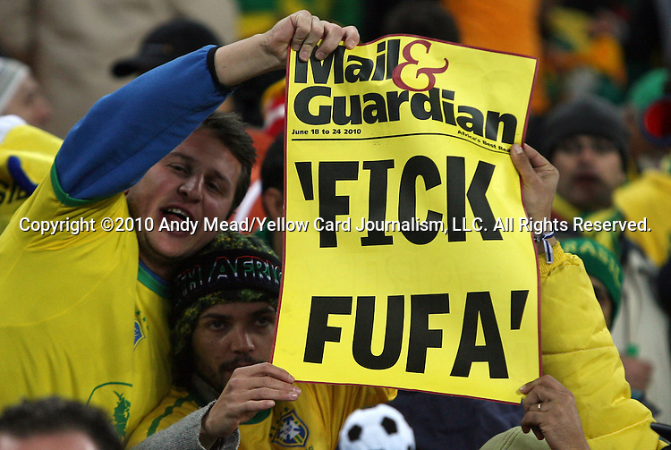 "20 JUN 2010: Brazil fans holding up a fake tabloid cover reading ""FICK FUFA"". The Brazil National Team played the C'ote d'Ivoire National Team at Soccer City Stadium in Johannesburg, South Africa in a 2010 FIFA World Cup Group G match."