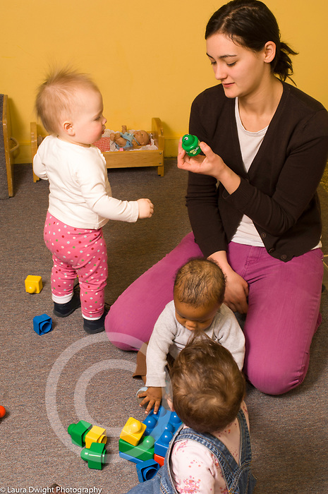 Day Care Center female caregiver with three babies, interacting with young toddler