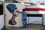 A Palestinian artist paints on a mural drawings of Pharaonic figure at a technical site in the southern Gaza Strip town of Rafah, near the border with Egypt, on June 1, 2017. Young artists Palestinian artists Nidal Al-Jarami and Wissam Makkawi recreated Egypt's landmark sites with mural paintings and sculptures, including the Pyramids of Giza and a remake of an Umm Kulthum Cafe, named after the late Egyptian diva who died in 1975. Photo by Mohammed Dahman