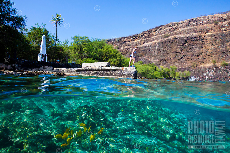 A woman preparing to jump into the water near the Captain Cook Monument at Kealakekua Bay, Big Island