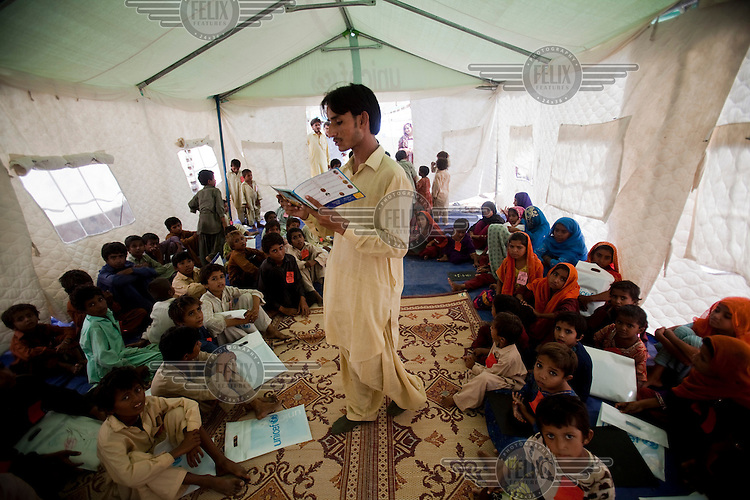 Children watch and listen as an educator takes a class at a Temporary Learning Centre (TLC) for flood affected children. TLCs have been set up throughout flood-affected areas in southern Pakistan by UNICEF to help children continue their education while they are displaced from their homes.